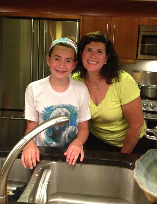 Mother and daughter at the sink in a Manhattan apartment washing dishes.