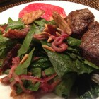Spinach salad with dates & almonds on a plate with broiled rib steak and an heirloom tomato slice.