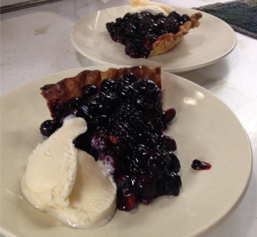 Best blueberry pie with blackberries, two pieces with vanilla ice cream.