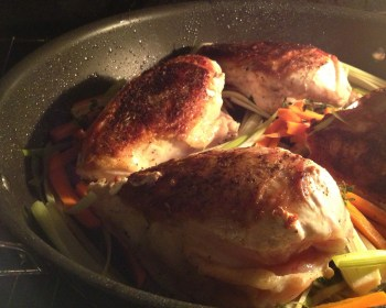 Chicken breasts with carrots and leeks in a skillet, roasting in the oven.