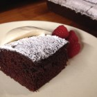 One piece of Made-in-the-Pan chocolate cake with vanilla ice cream and fresh raspberries.