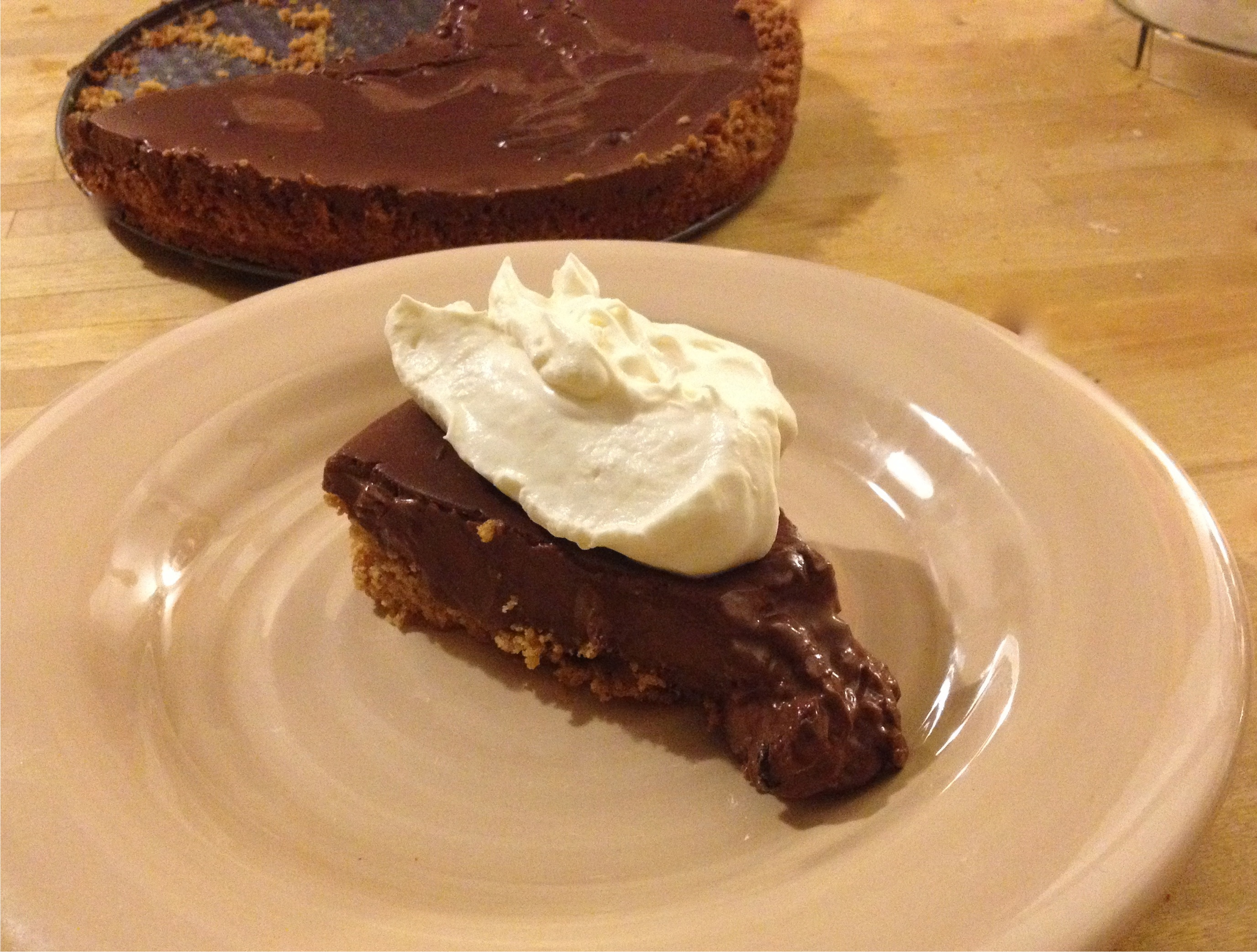 Chocolate tart with a graham cracker crust and whipped cream.