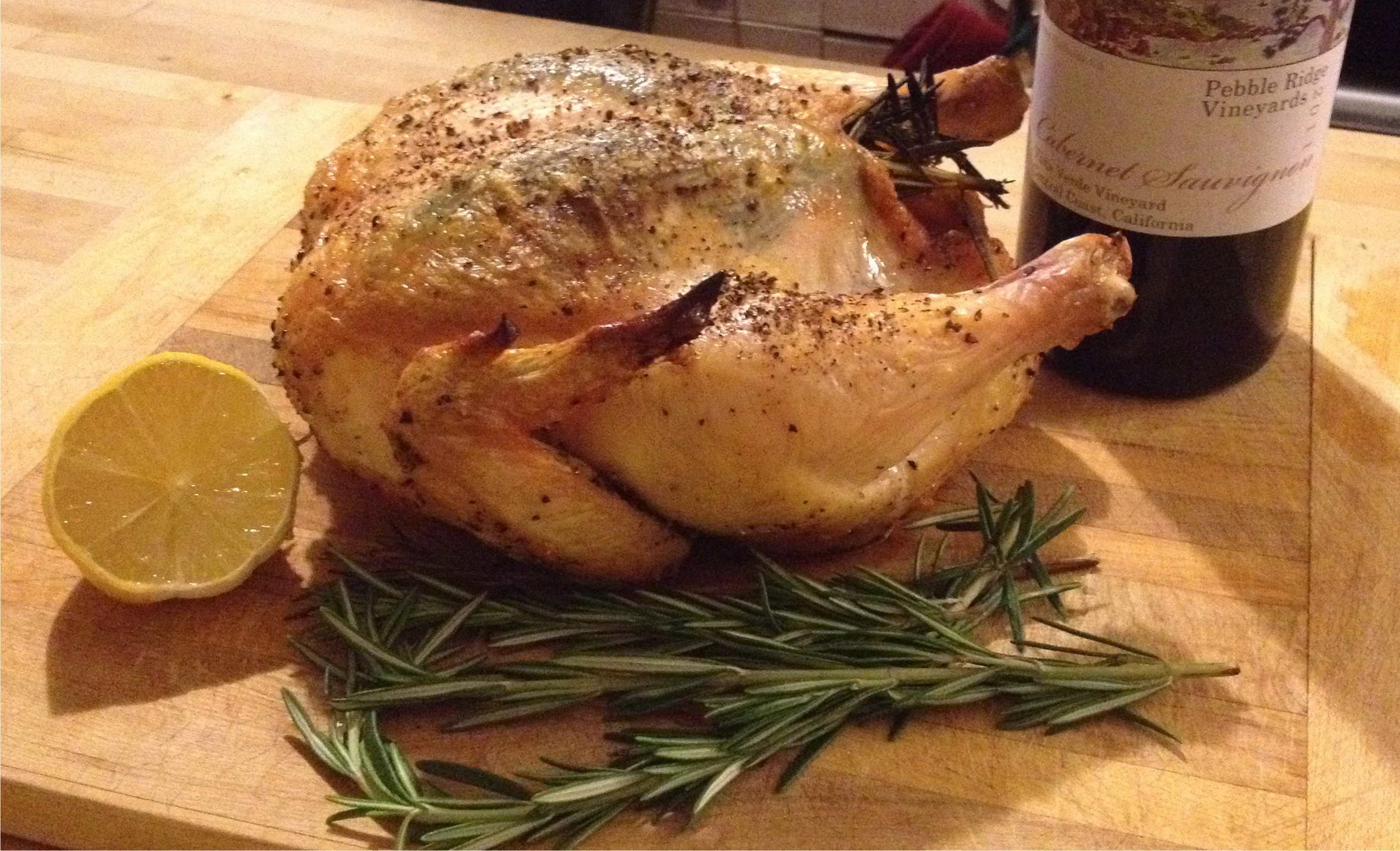 Roasted chicken on a board with rosemary and lemon garnish.