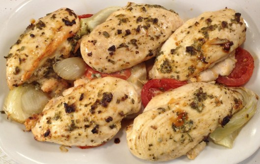 Chicken breasts roasted on tomatoes and fennel on a white platter.