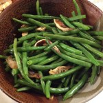 Green beans and shittake mushrooms in a brown pottery bowl.