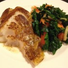 Kale with ginger and carrots and roasted cod on a white Wedgewood plate.