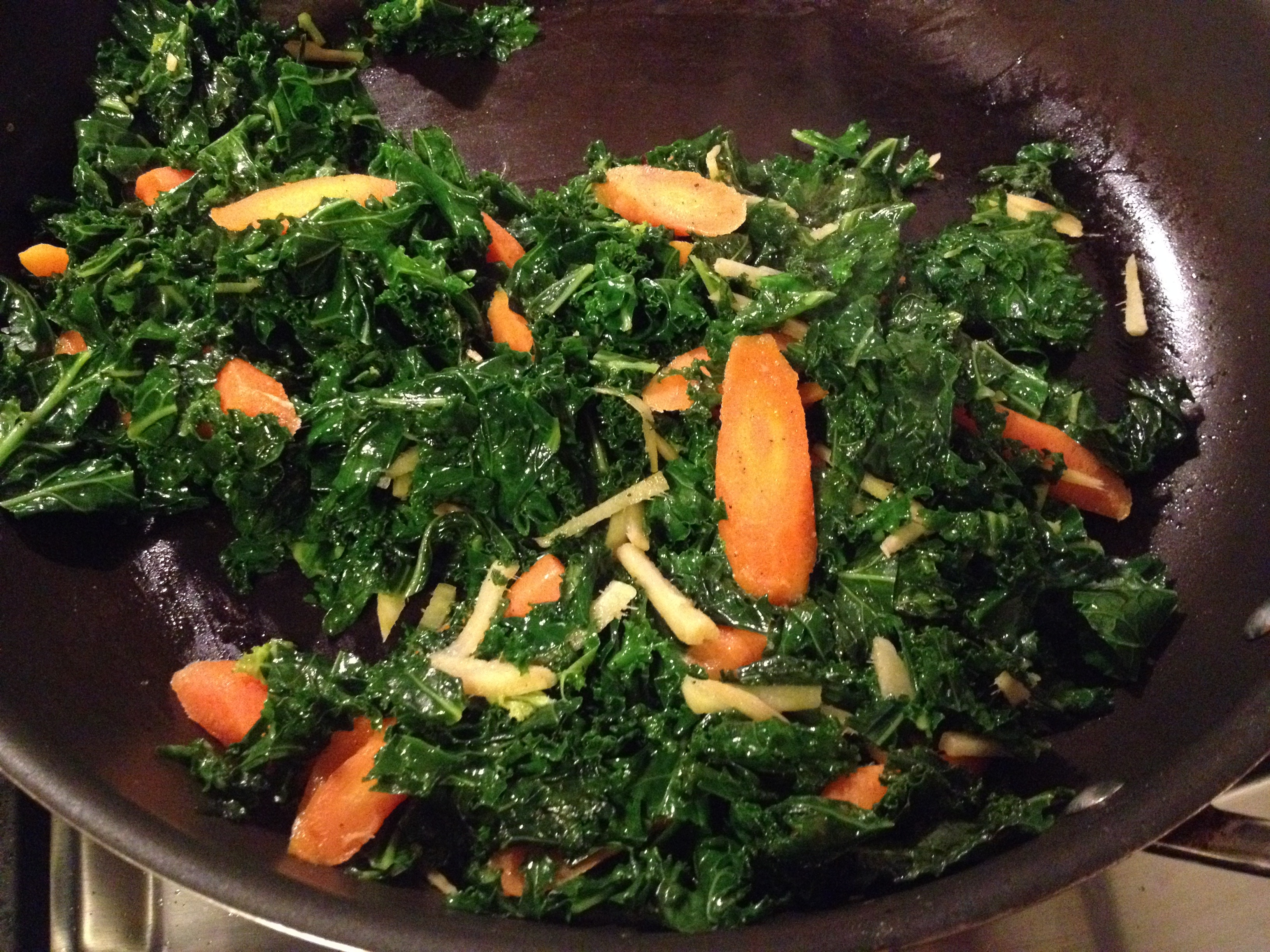 Kale with ginger and carrots in skillet.