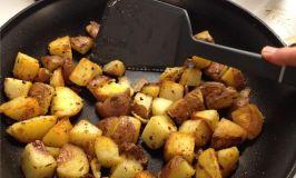 Calphalon serrated spatula cutting a potato.