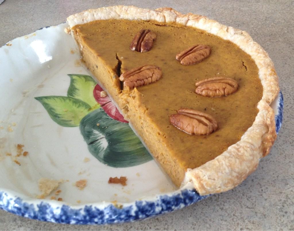 Pumpkin pie half cut.