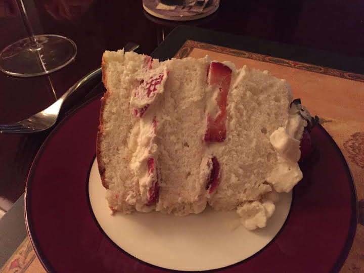Huge piece of angel food cake with whipped cream and strawberries.