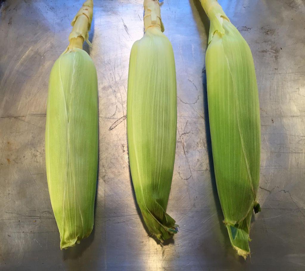 Corn on a baking sheet.