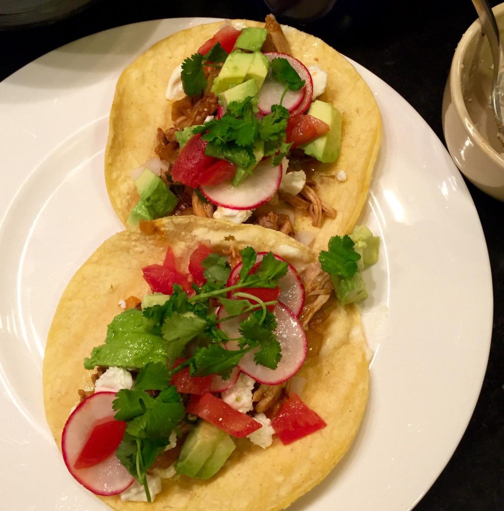 Weeknight chicken tacos finished on a white plate.