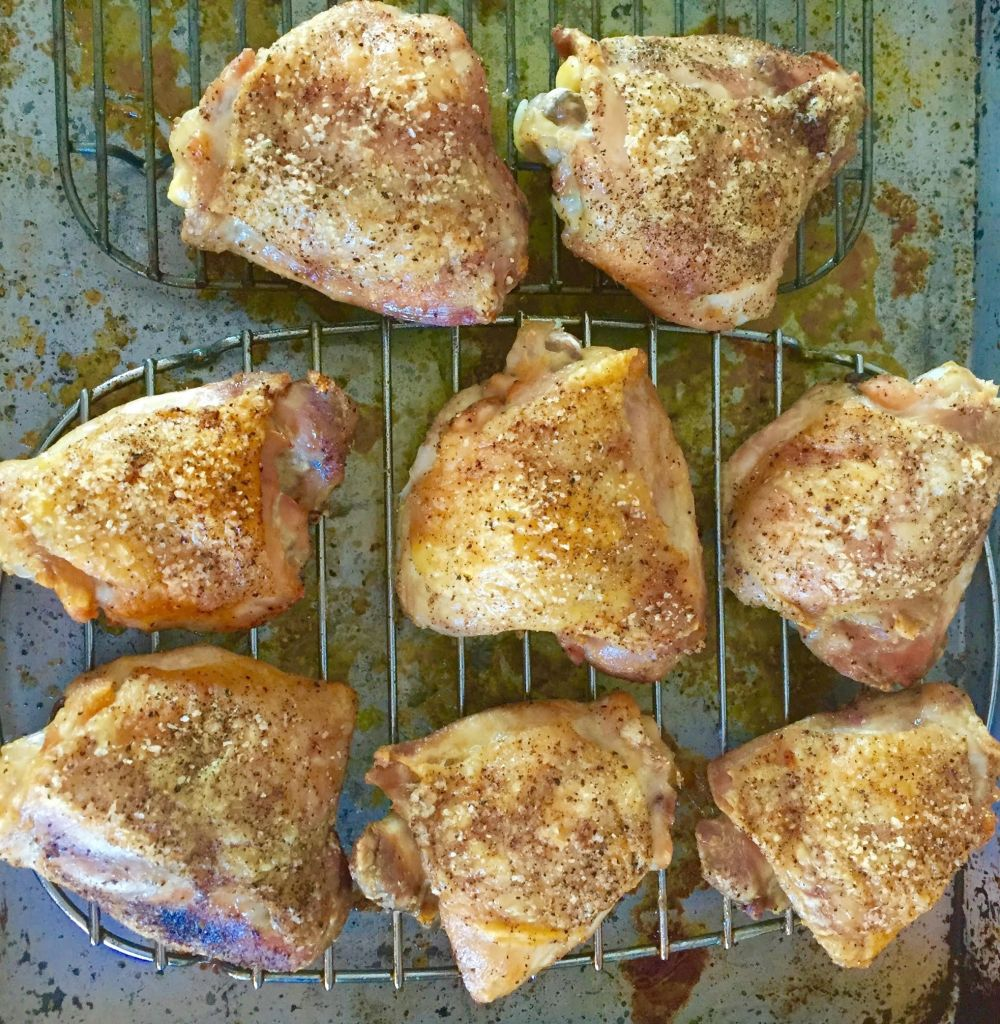 Roasted chicken thighs on a rack.