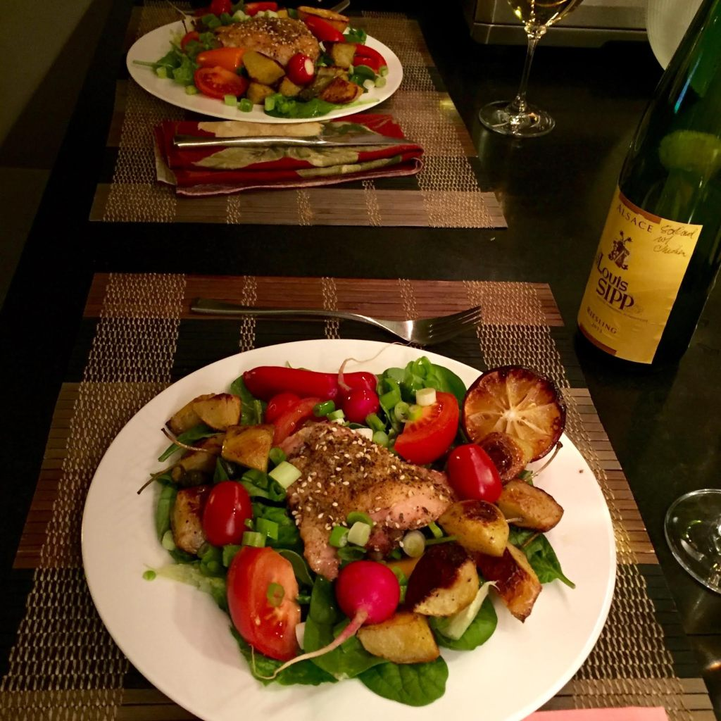 Two dinner salads with chicken thighs and white wine.