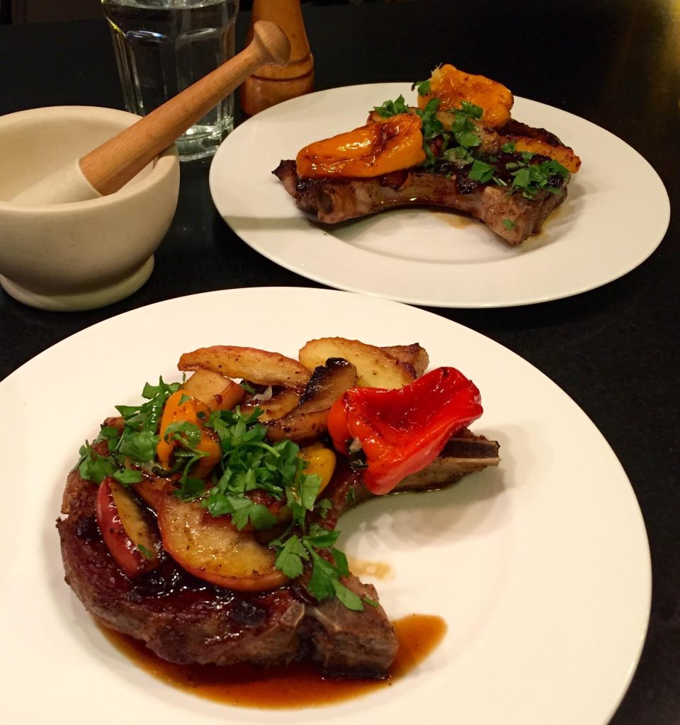 English Provender Caramelized Red Onion Chutney on pork chops on 2 plates with peppers and apples.