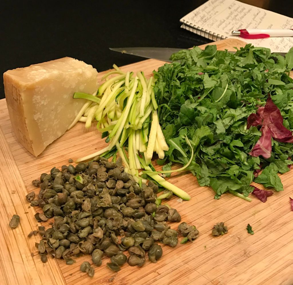 Hunk of Parmigiano cheese, chopped hearty greens, drained and chopped capers, and julienned zucchini on a wooden board, handwritten recipe in background.