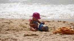 Baby speelt op strand.