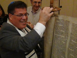Cantor Neil Schnitzler unrolls a Holocaust surviving Torah scroll at Temple Emanuel