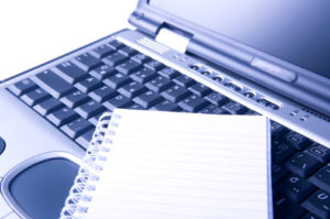 A writing pad sits on top of a laptop symbolic of how online copy is different from print copy.