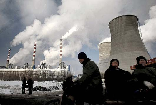 Workers sit in front of carbon-spewing stacks creating global warming