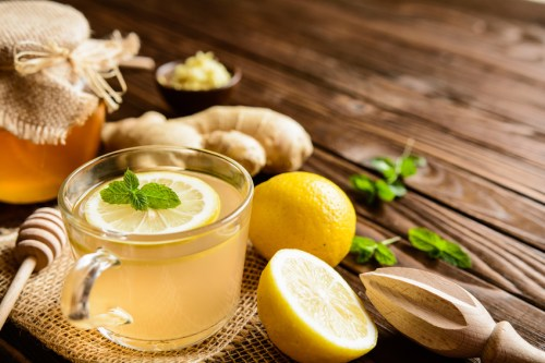Cup of ginger root tea with lemon, honey and mint on a wooden background