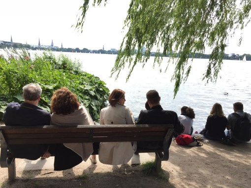 Locals crowd the banks of the Outer Alster Lake on a warm summer day in Hamburg.