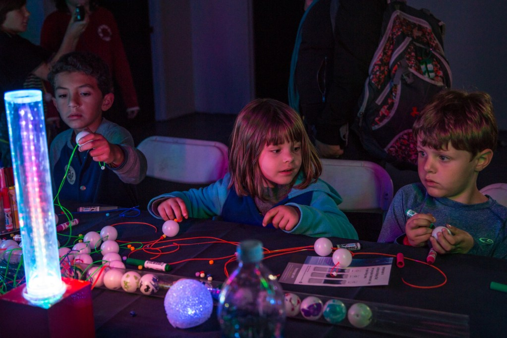 Children work together to create blacklight jewelry in the Dark Room.