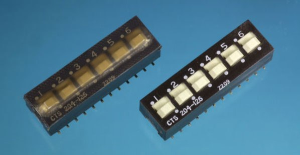 Figure 6-17. A SPDT surface-mount double-throw DIP switch, sold with a plastic cover (shown at left) to protect it during wave soldering. The cover has been removed at right.