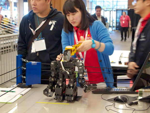 A weight-lifting contestant prepares her bot.