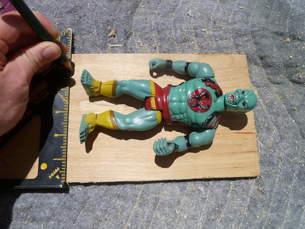 I decided to make a Mumm-Ra-sized box today, so laid him out on the plywood and gave him plenty of wiggle room. Use a speed square to make your cut line.