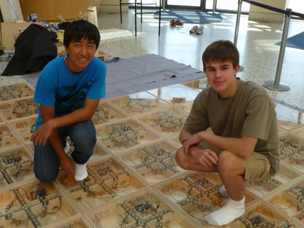 Young makers Andrew Ke and Matthew Tung show off the FlowX26, a giant light-up floor made for interactive games.