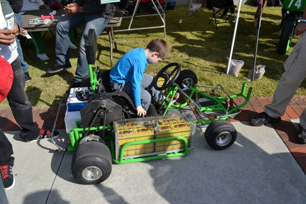 A young attendee tries one of the SPSU Electric Vehicle Team's vehicles on for size.