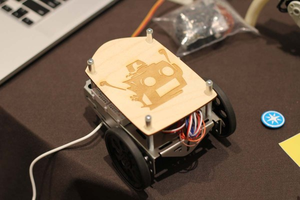 A bot under construction with a custom laser-cut part that includes the RobotsConf logo.