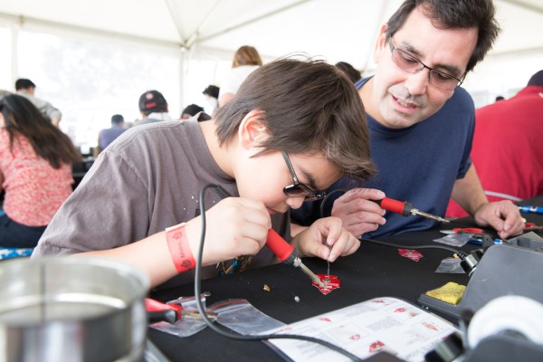 Christian Phillips and his father, Gary, from San Carlos learn to solder.