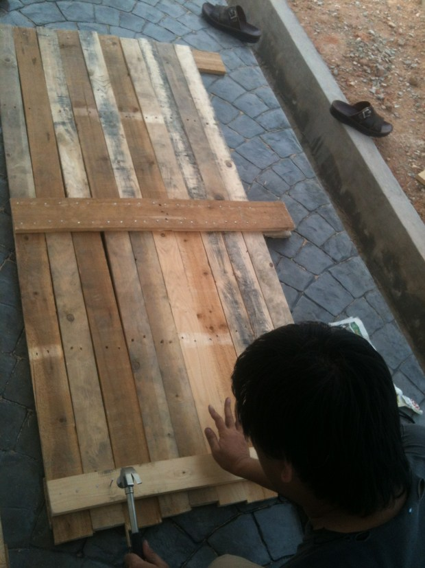 I dismantled the wood pallets and arrange them based on the door measurements. 2 wood pallets seemed enough.