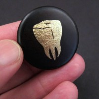 Josh Ellingson's Gold Tooth Button makes creative use of gold leaf wrapped in a transparency printed with his design.