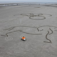 Those posts embedded in the sand help the robot orient its position as well as the picture placement.