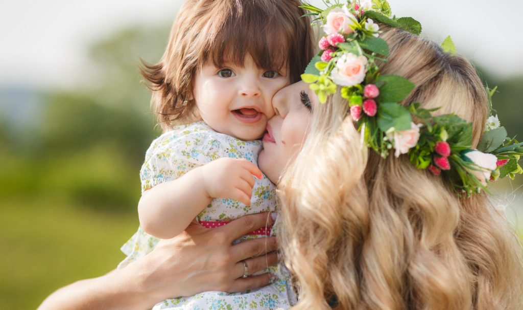 Young beautiful mother, model,blonde with lush, long hair,beautiful makeup,on her head a wreath of flowers, plays on a green meadow in summer with a young daughter,a girl with brown eyes and luxuriant hair,Sunny day ** Note: Soft Focus at 100%, best at s
