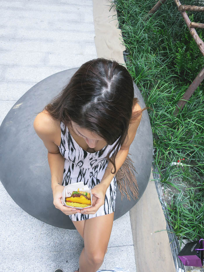 girl eating a ramen burger in Bangkok