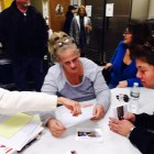 Group leaders Susan Markkievitz, left, and Heidi Sanderson, center, discuss a postcard campaign for a NH law to support Narcan access during a recent TAM meeting in Derry.