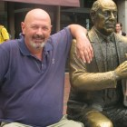 Journalist Roger Carroll is pictured with statue of Red Auerbach in Boston.
