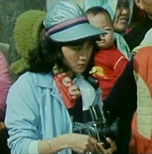 Xinghui with a blue hat and a camera, played by Fong Fei-fei