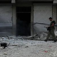 Free Syrian Army soldier walking among rubble in Aleppo. Zdroj:  commons.wikimedia.org