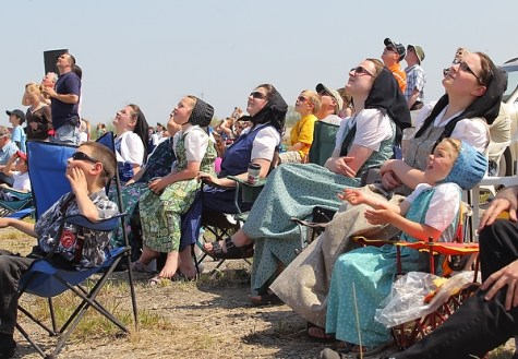 Members of Sprucewood Colony look towards the sky while watching the Canadian Forces Snowbirds aerial demonstration near Neepawa Airport on Saturday afternoon.  (Tim Smith/Brandon Sun)