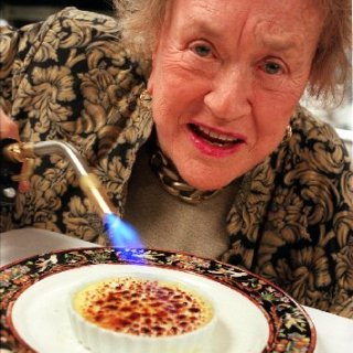 Julie Child using a kitchen torch on her creme brulee.