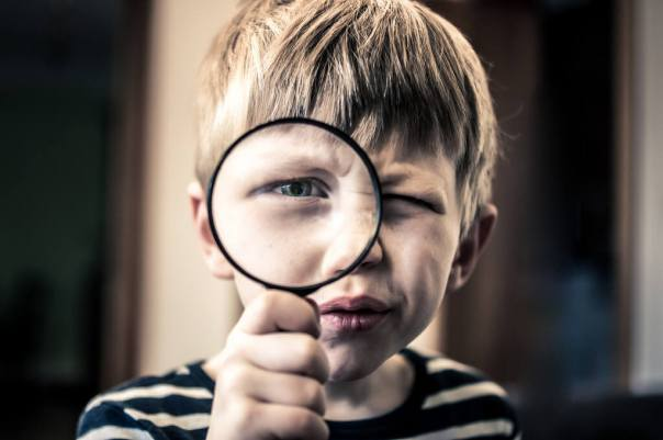 A small boy holding a magnifying glass as if to say: I'm searching for you, where are you? - Photo by baranco1