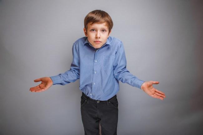 teenager boy shrugs at a loss and