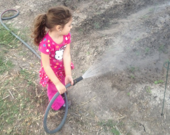 A future farmer helps tend her family's plot in the H.O.P.E. community garden