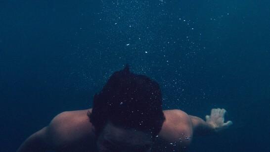 水の中で沈む男性