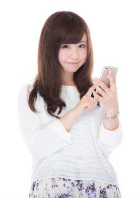 携帯電話(スマホ)をタッチ操作する女性